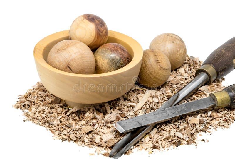 bolas de madera Mano-dadas vuelta en un cuenco adornado con serrín y la herramienta foto de archivo libre de regalías