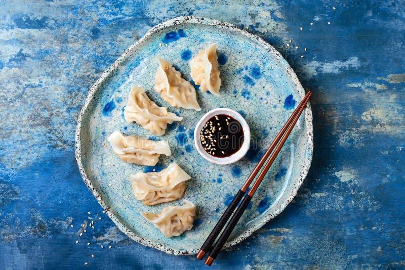 Bolas de masa hervida asiáticas con la salsa de soja, las semillas de sésamo y los palillos Bolas de masa hervida del dim sum del foto de archivo
