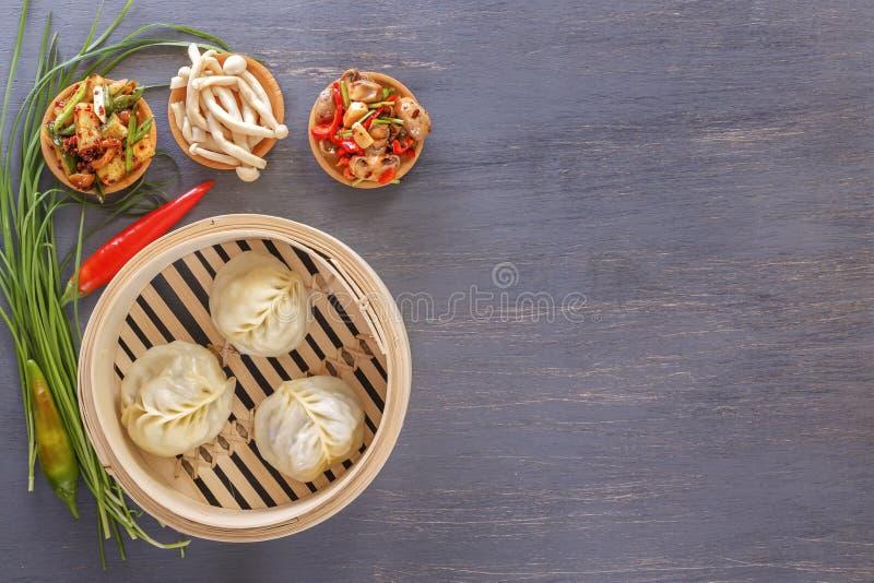 Bolas de masa hervida asiáticas del vapor - un plato tradicional de uvas chinas con los aperitivos vegetales calientes imagen de archivo libre de regalías