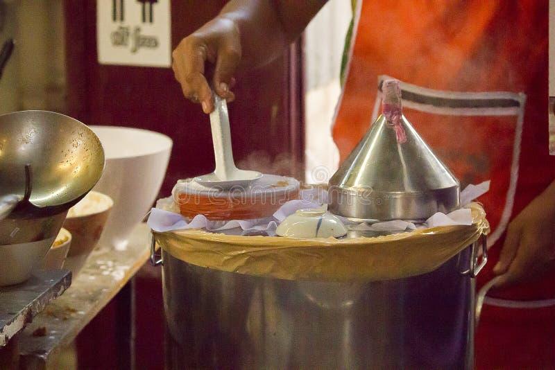 Bolas de masa hervida cocidas al vapor tailandesas de la arroz-piel estirando la tela en la boca del pote imagen de archivo