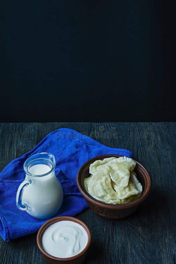 Bolas de masa hervida con las patatas y la col Crema agria, leche y verdes Plato tradicional de Ucrania Fondo de madera oscuro fotos de archivo libres de regalías