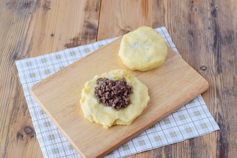 Bolas de masa hervida de la patata rellenas con la carne picadita en una tabla de cortar de madera paso a paso cocinando Concepto fotos de archivo