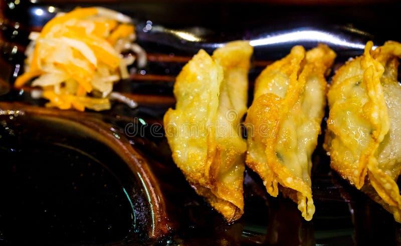 Bolas de masa hervida fritas en la salsa de la placa y de soja Asiático hecho en casa Vegeterian Potstickers con la salsa y el ce imagenes de archivo