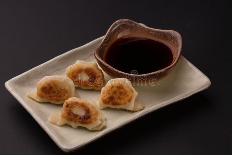 Bolas de masa hervida de Gyoza, comida japonesa popular en fondo negro fotos de archivo libres de regalías