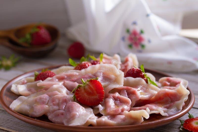 Bolas de masa hervida, llenadas de las fresas Varenyky, vareniki, pierogi, pyrohy - bolas de masa hervida con el relleno fotografía de archivo libre de regalías