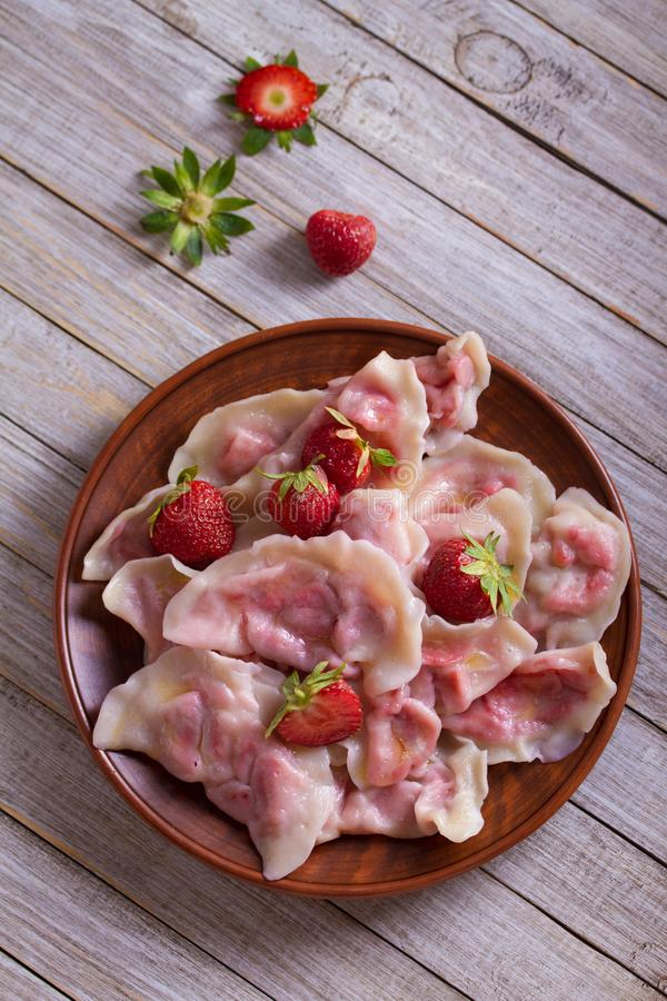 Bolas de masa hervida, llenadas de las fresas Varenyky, vareniki, pierogi, pyrohy - bolas de masa hervida con el relleno fotos de archivo