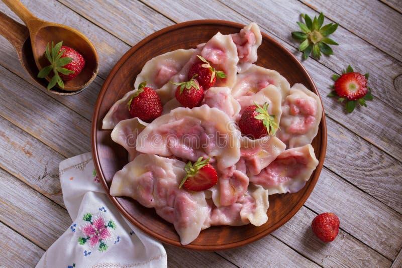 Bolas de masa hervida, llenadas de las fresas Varenyky, vareniki, pierogi, pyrohy - bolas de masa hervida con el relleno imagenes de archivo