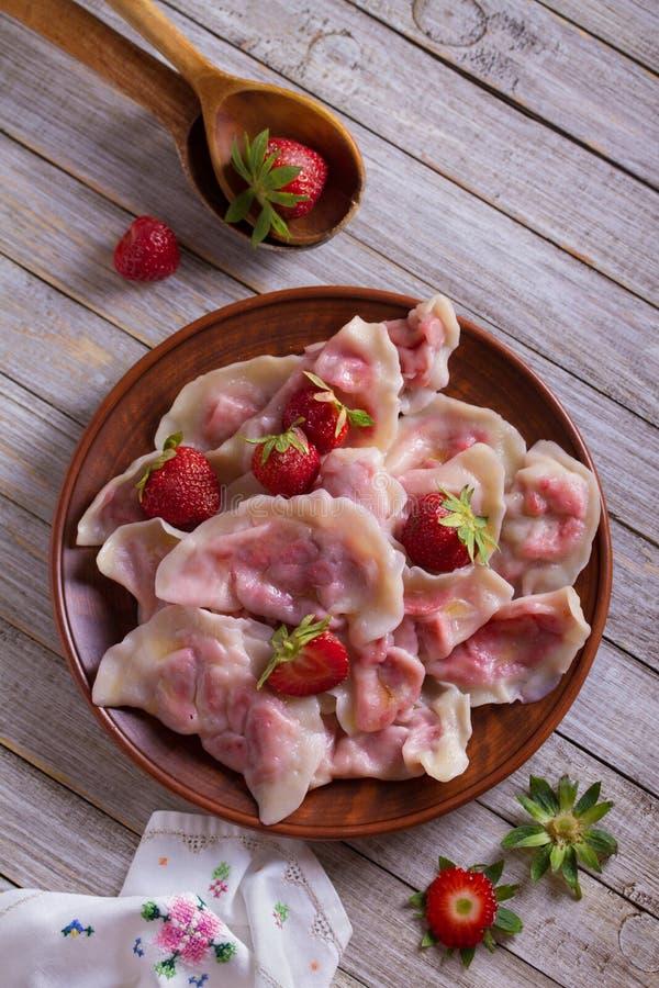 Bolas de masa hervida, llenadas de las fresas Varenyky, vareniki, pierogi, pyrohy - bolas de masa hervida con el relleno imágenes de archivo libres de regalías