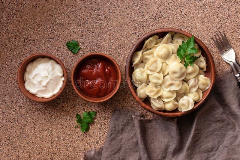 Bolas de masa hervida rusas de la carne del pelmeni de la comida con la crema agria y la salsa de tomate dispuestas en fila en fo imagen de archivo libre de regalías
