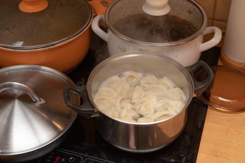 Bolas de masa hervida sabrosas en un pote del metal en una cocina eléctrica Platos preparados para los días de fiesta imagenes de archivo