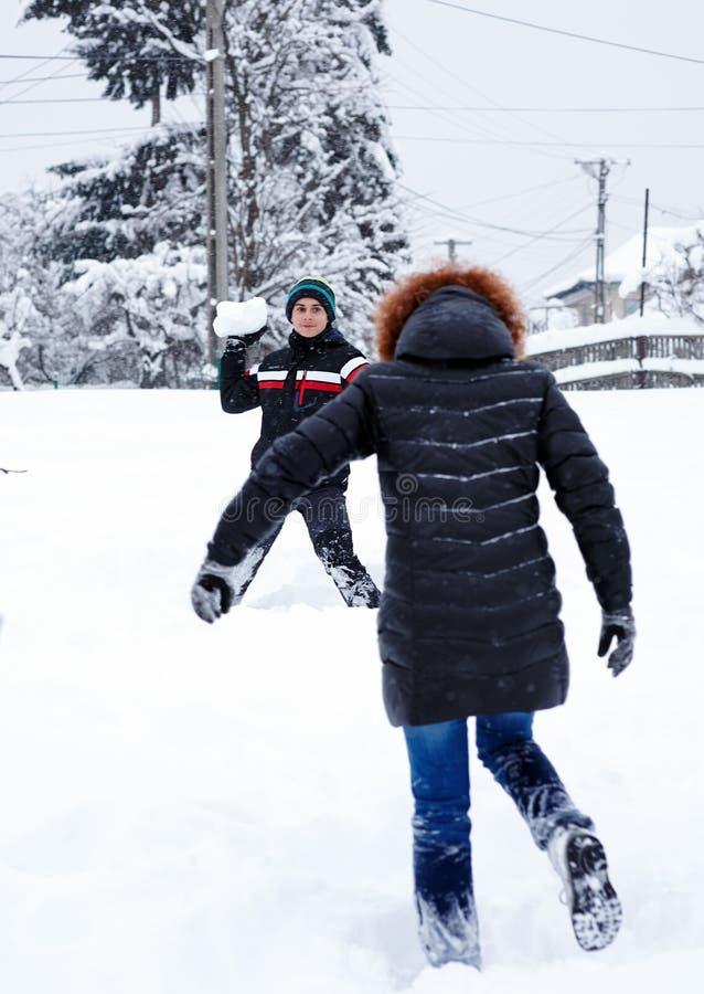Bolas de neve de jogo do adolescente fotografia de stock