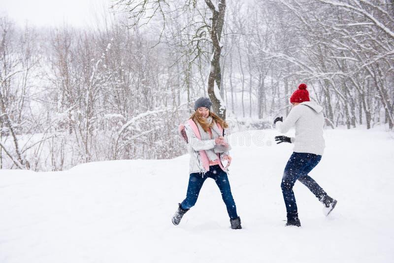 Bolas de nieve del juego de la gente joven en bosque del invierno imagen de archivo