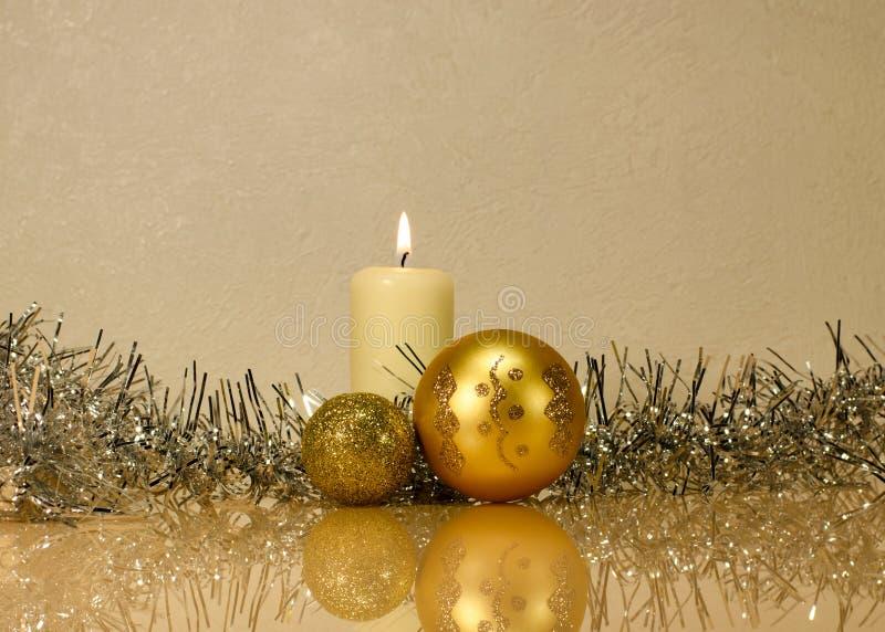 Bolas de oro de la Navidad en el fondo de una vela ardiente adentro imagenes de archivo