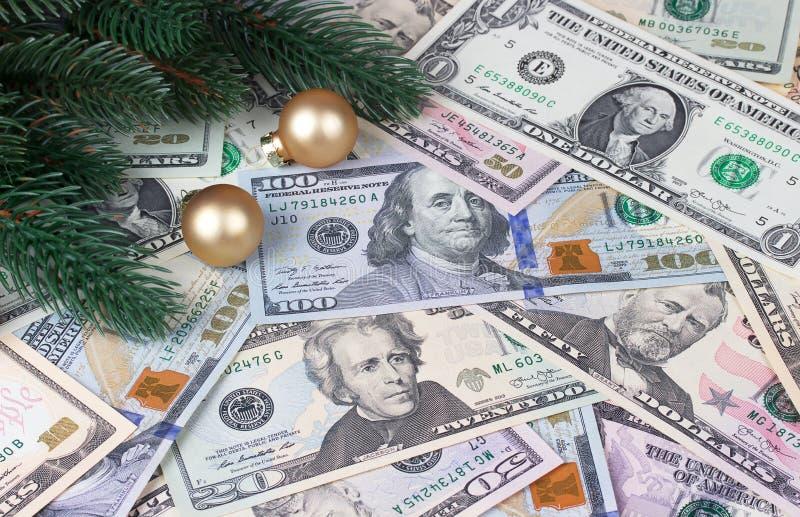 Bolas de oro de las ramas de árbol de navidad en fondo del dinero foto de archivo