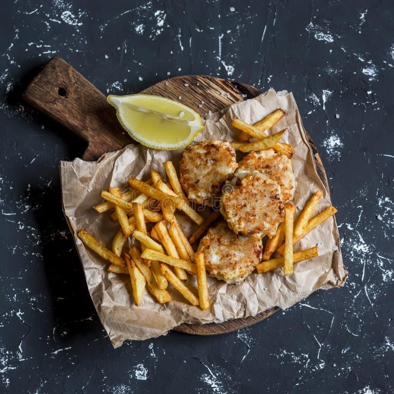Bolas de peixes e microplaquetas de batata na placa de corte rústica em um fundo escuro imagem de stock