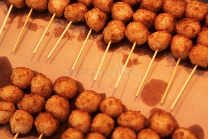 Bolas de peixes fritadas em espetos para a venda imagem de stock