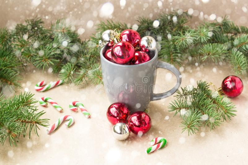 Bolas de plata y rojas de las decoraciones de la Navidad en taza con el árbol de abeto y el fondo de la Navidad de la nieve foto de archivo libre de regalías