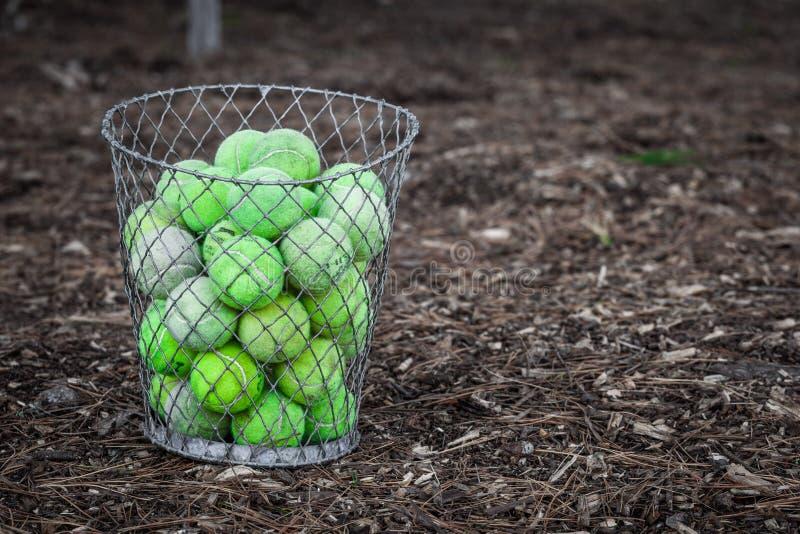 Bolas de tênis desvanecidas velhas empilhadas acima na cesta de fio do metal imagem de stock