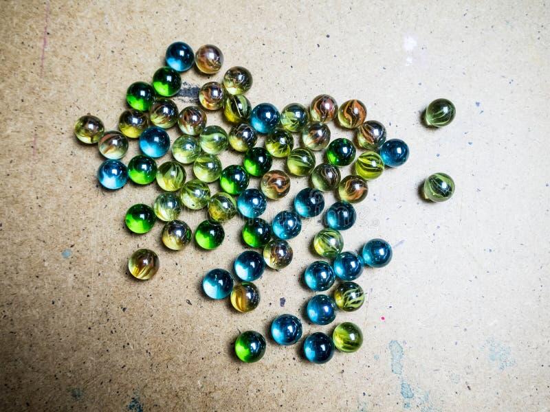 Bolas de vidrio coloreadas dispersadas en una superficie de madera foto de archivo libre de regalías