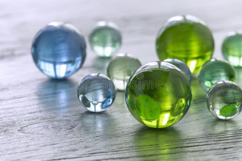 Bolas de vidro de verde e de azul em uma superfície de madeira imagem de stock