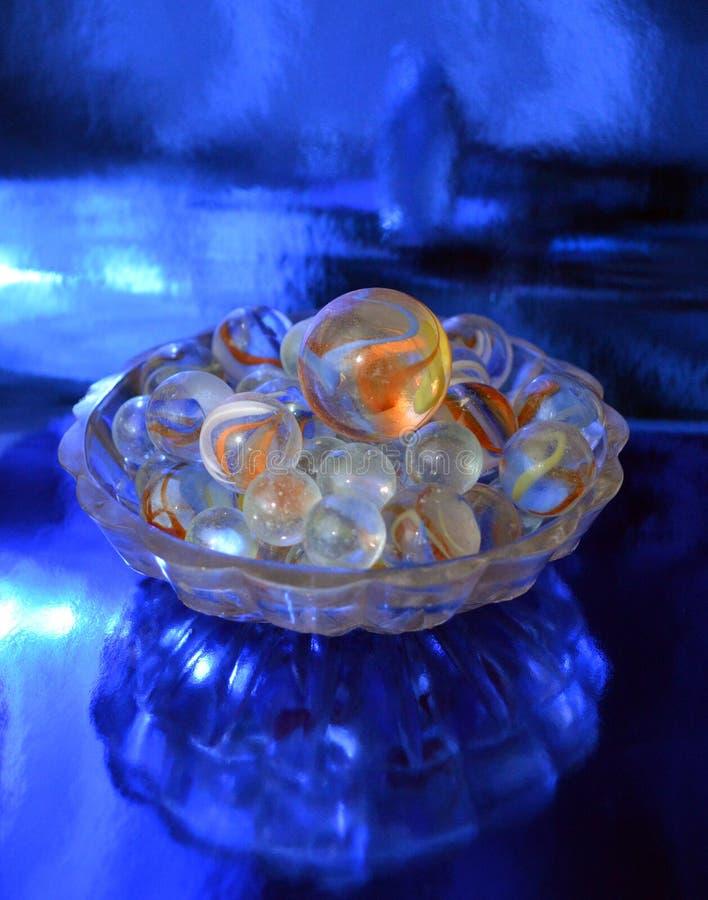 Bolas de vidro em um vaso pequeno em um fundo metalizado azul foto de stock