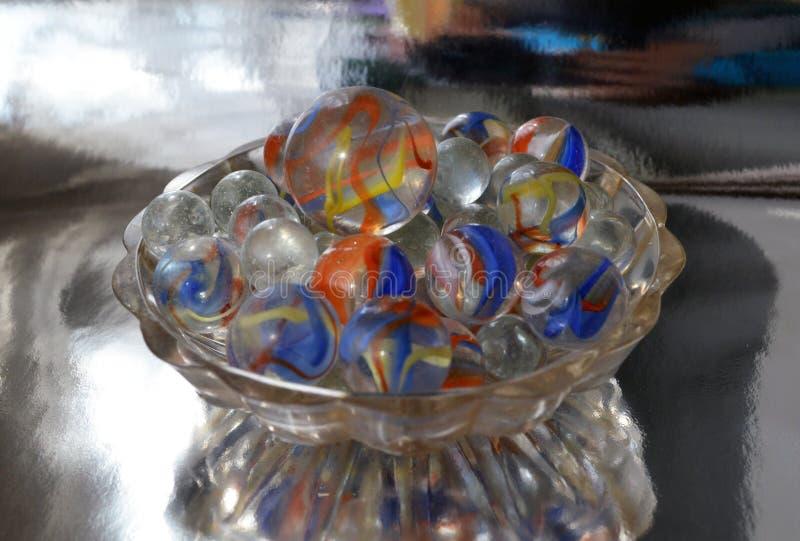 Bolas de vidro em um vaso pequeno em um fundo metalizado fotografia de stock royalty free