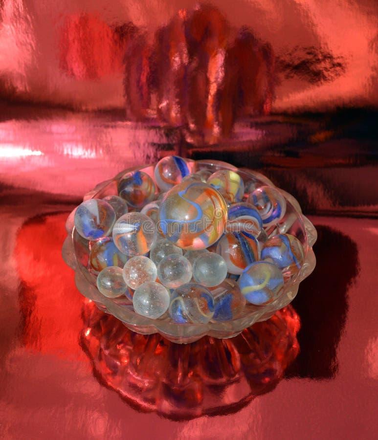 Bolas de vidro em um vaso pequeno em um fundo metalizado vermelho foto de stock royalty free