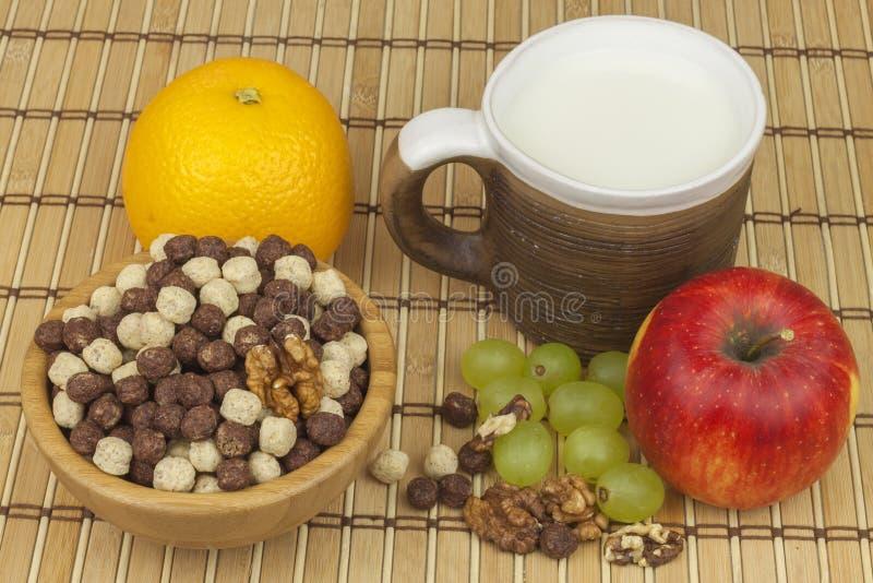 Bolas del cereal del chocolate en un cuenco de bambú Desayuno sano con la fruta y la leche Una dieta por completo de la energía y fotografía de archivo