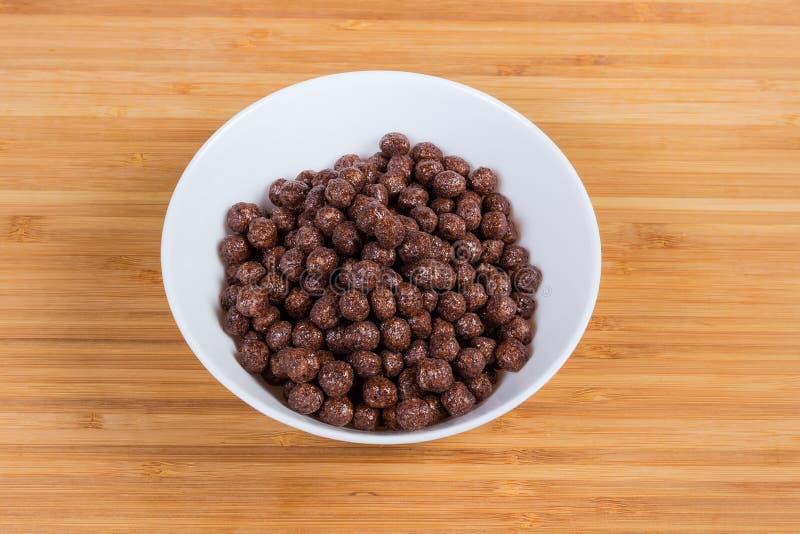 Bolas del chocolate del cereal de desayuno en cuenco en una superficie de madera fotos de archivo