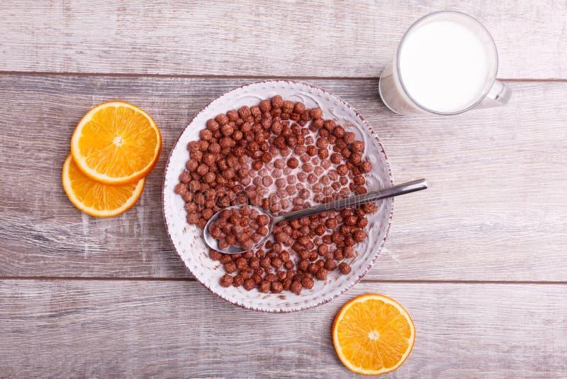 Bolas del chocolate del cereal en cuenco con leche Fruta cítrica cortada en una tabla imágenes de archivo libres de regalías
