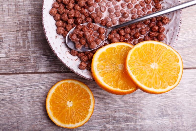 Bolas del chocolate del cereal en cuenco con leche Fruta cítrica cortada en una tabla imagenes de archivo