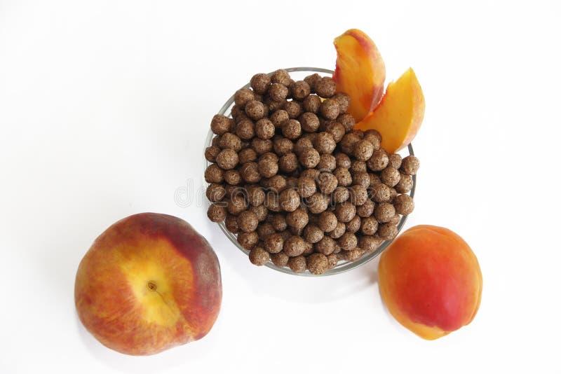 Bolas del maíz del chocolate dulce en la placa de cristal y el melocotón en un fondo blanco fotografía de archivo libre de regalías