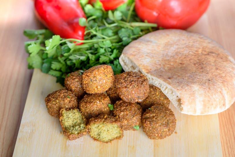 Bolas do Falafel, pimenta vermelha doce, pão pão árabe-árabe e salsa fresca verde no fundo rústico de madeira imagens de stock royalty free