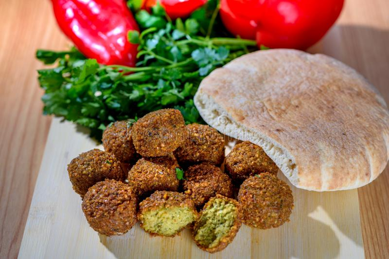 Bolas do Falafel, pimenta vermelha doce, pão pão árabe-árabe e salsa fresca verde no fundo rústico de madeira imagens de stock