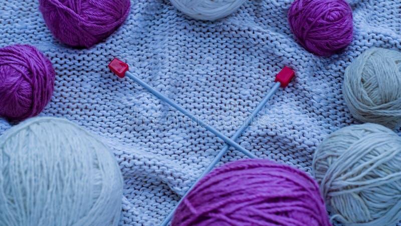 Bolas do fio de lã para fazer malha na tabela Roupa morna louca foto de stock