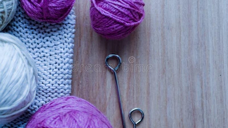 Bolas do fio de lã para fazer malha na tabela Roupa morna louca fotografia de stock