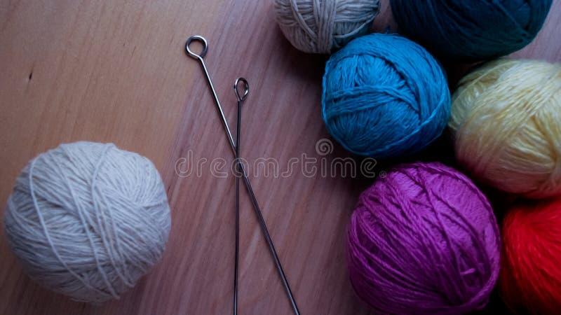 Bolas do fio de lã para fazer malha na tabela Roupa morna louca imagem de stock