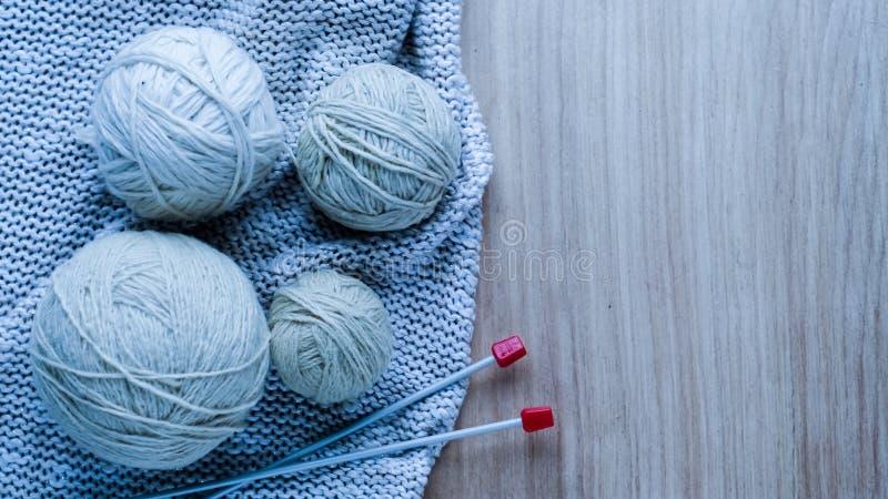 Bolas do fio de lã para fazer malha na tabela Roupa morna louca fotos de stock