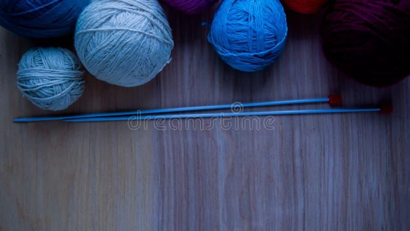 Bolas do fio de lã para fazer malha na tabela Roupa morna louca imagens de stock