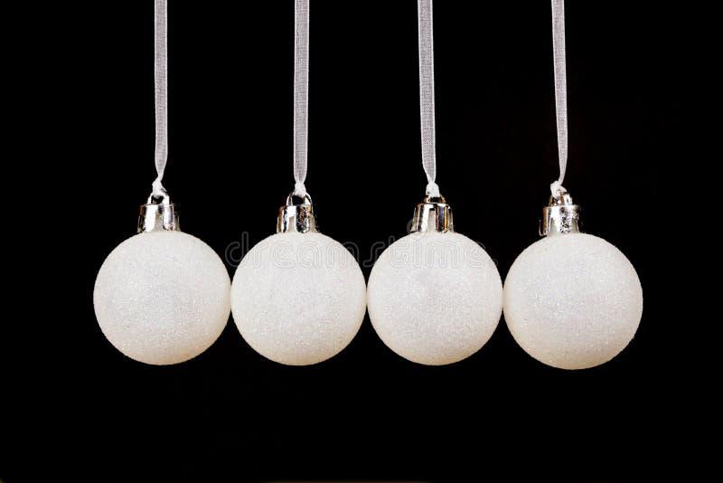Bolas do White Christmas que penduram em seguido no fundo preto foto de stock royalty free