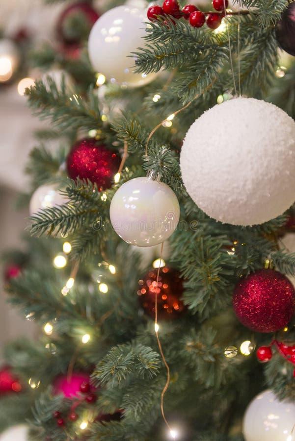 Bolas dos brinquedos do Natal, as vermelhas e as brancas com luzes na árvore de Natal, ramos do abeto foto de stock royalty free