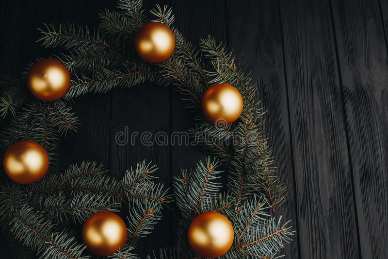 Bolas douradas das decorações do brinquedo do Natal ou do ano novo e ramo de árvore da pele rústico no fundo de madeira, vista su imagens de stock