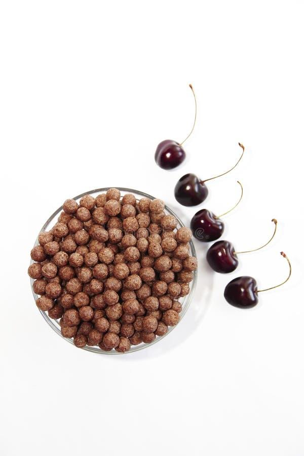 Bolas dulces del chocolate del maíz en una placa de cristal y bayas de la cereza en un fondo blanco fotos de archivo libres de regalías