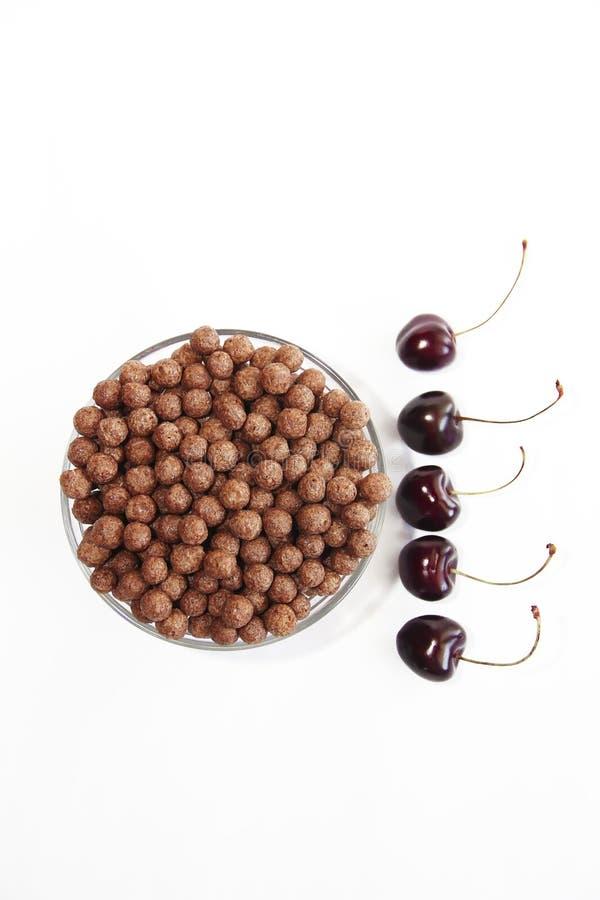 Bolas dulces del chocolate del maíz en una placa de cristal y bayas de la cereza en un fondo blanco imagen de archivo libre de regalías