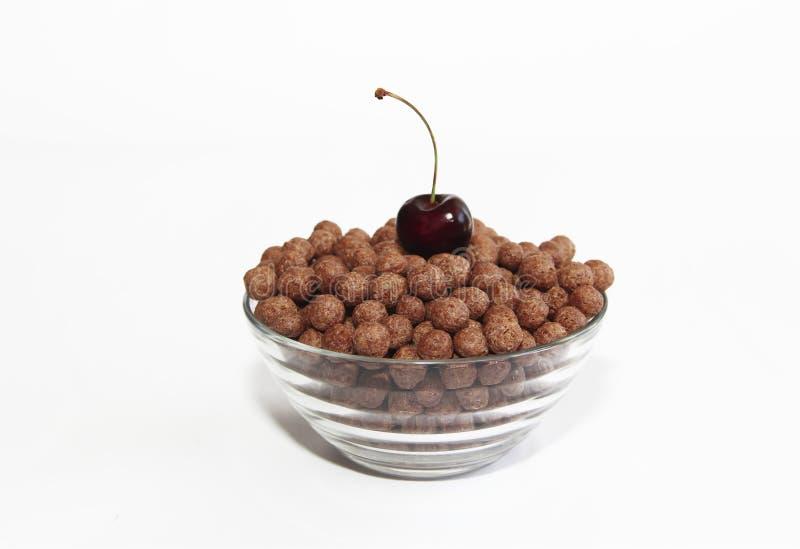 Bolas dulces del chocolate del maíz en una placa de cristal y bayas de la cereza en un fondo blanco fotografía de archivo