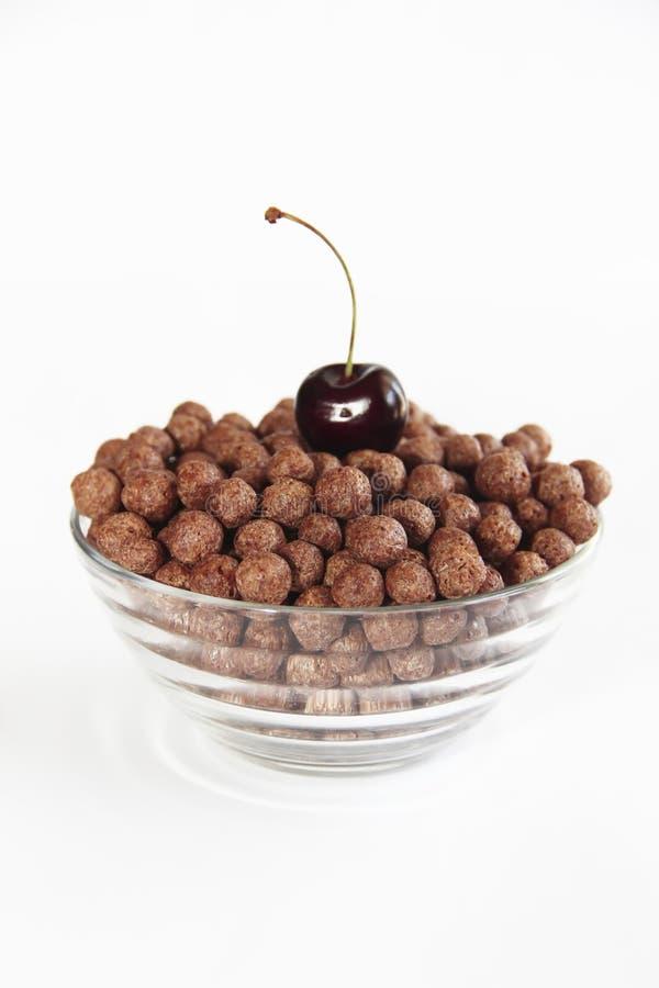 Bolas dulces del chocolate del maíz en una placa de cristal y bayas de la cereza en un fondo blanco imagenes de archivo