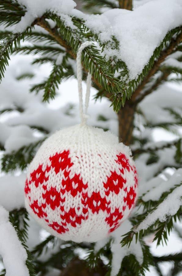 Bolas feitas malha para decoração da árvore de ano novo e de Natal que pendura no ramo do abeto vermelho coberto com a neve imagens de stock royalty free