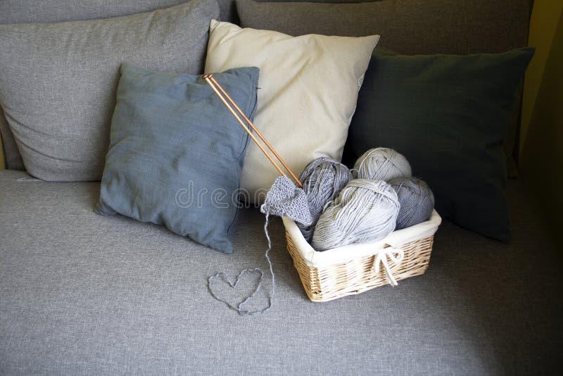 Bolas grises de lanas y de agujas que hacen punto en un soporte de la cesta en un sofá gris con las almohadas foto de archivo libre de regalías