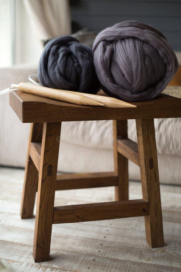 Bolas grises de las lanas con las agujas que hacen punto de madera en silla de madera en i acogedor imágenes de archivo libres de regalías