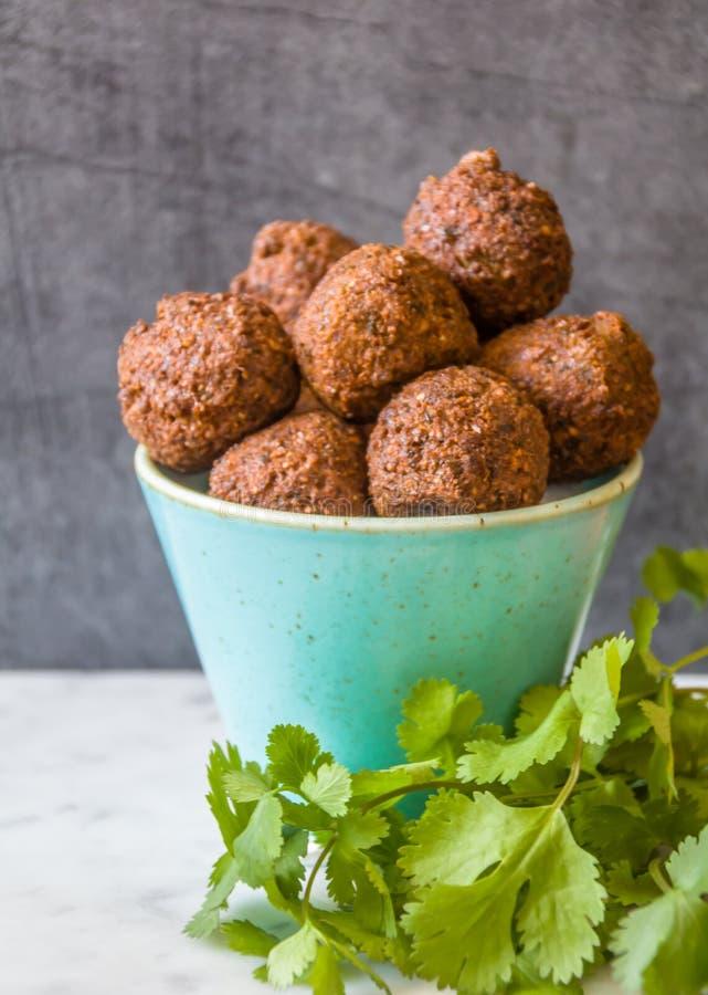 Bolas hechas en casa tradicionales del Falafel del garbanzo en un cuenco con las hojas y semillas, pimienta roja y col, pan del c imágenes de archivo libres de regalías